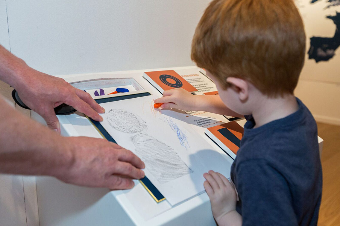 Boy discovering the past through coin rubbings at the Waterloo Lives exhibition
