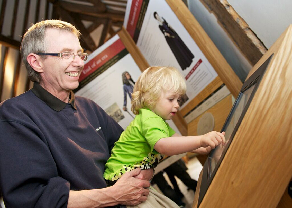 Visitors of all ages learning from interactive exhibition screens
