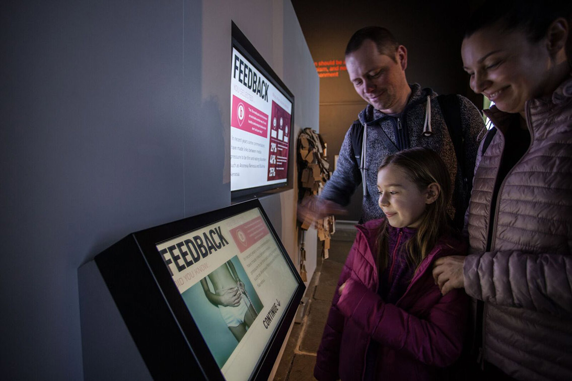 Young family learning from digital interactive screens