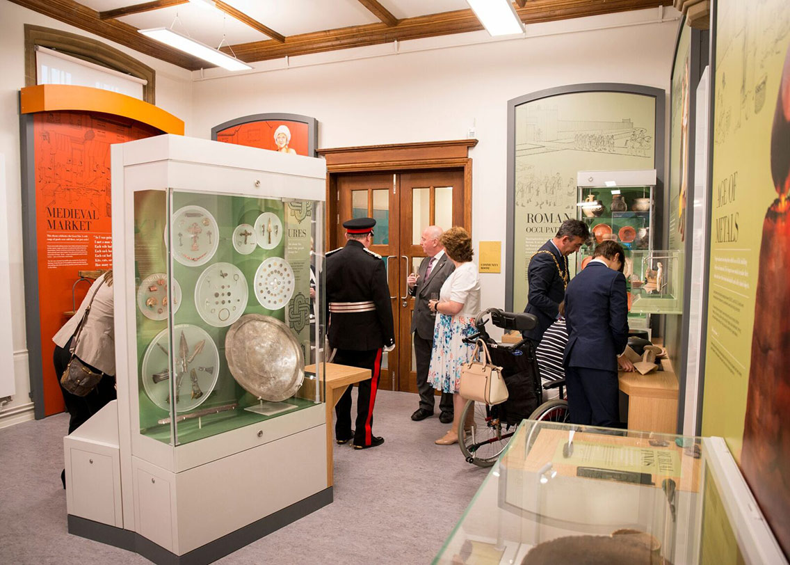 Visitors exploring medieval and Roman exhibition artefacts