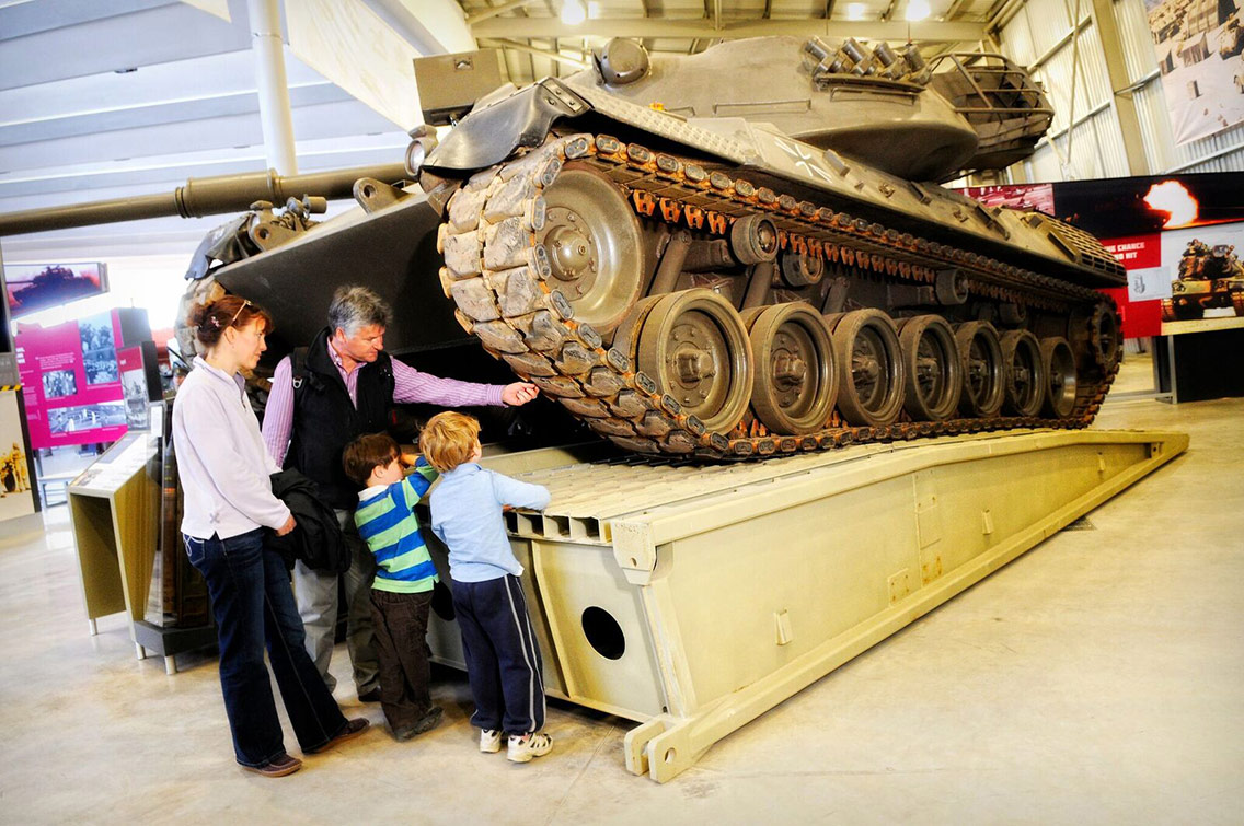 Exhibition visitors exploring the continuous track of a military tank